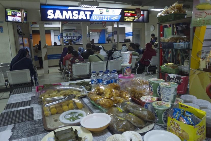 Wajib pajak menunggu pengurusan perpanjangan Surat Tanda Nomor Kendaraan (STNK) di Samsat Outlet di pusat perbelanjaan ITC Depok, Jabar, Kamis (30/3).