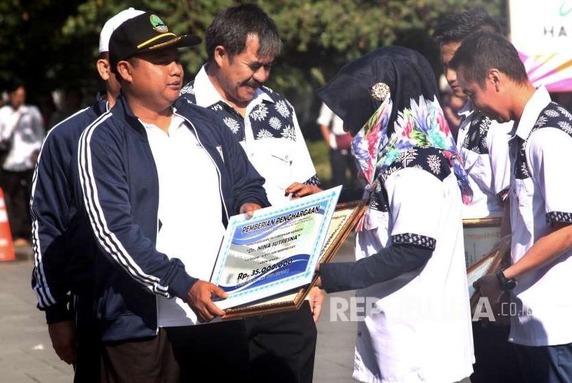 Wakil Gubernur Jabar Uu Ruzhanul Ulum memberikan penghargaan berupa Uang Kadeudeuh kepada atlet berprestasi, pelatih berprestasi, wasit, mantan olahragawan, guru olahraga, ilmuan, pembina, organisasi dan wartawan olahraga pada Peringatan Hari Olahraga Nasional 2018, di halaman Gedung Sate, Kota Bandung, Senin (10/9).
