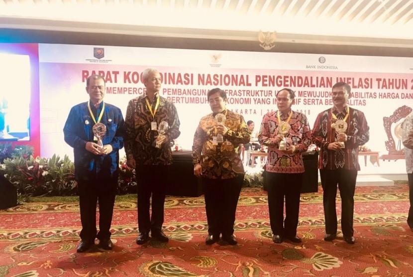 Wakil Gubernur Sumbar Nasrul Abit (kiri), mewakili Gubernur Sumbar, menerima penghargaan TPID Terbaik Provinsi di Kawasan Sumatra 2017.