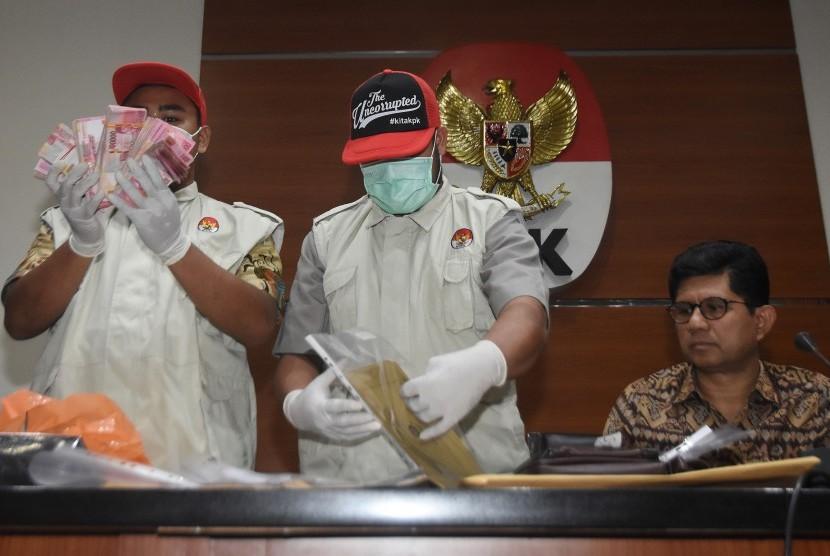 Wakil Ketua KPK Laode M. Syarief (kanan) bersama penyidik menunjukkan barang bukti hasil OTT kasus dugaan suap terkait seleksi pengisian jabatan pimpinan tinggi di Kementerian Agama saat konferensi pers di gedung KPK, Jakarta, Sabtu (16/3).