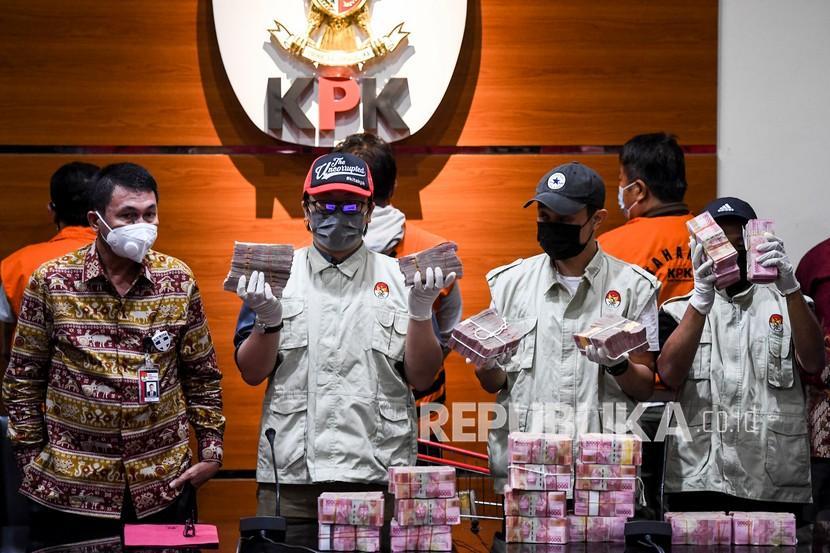 Wakil Ketua KPK Nawawi Pomolango (kiri) menyaksikan penyidik KPK menunjukan barang bukti berupa uang tunai saat konferensi pers Operasi Tangkap Tangan (OTT) Bupati Banggai Laut Wenny Bukamo di gedung KPK, Jakarta, Jumat (4/12/2020). Dalam OTT di Kabupaten Banggai Laut dan Kabupaten Luwuk, Sulawesi Tengah pada Kamis (3/12), KPK menetapkan Bupati Banggai Laut Wenny Bukamo dan lima orang lainnya sebagai tersangka kasus dugaan suap pengadaan barang dan jasa di lingkungan Pemkab Banggai Laut dan mengamankan uang tunai sebesar Rp2 miliar dan diduga uang tersebut digunakan untuk dana kampanye Wenny Bukamo yang maju sebagai petahana pada Pilkada Kabupaten Banggai Laut.