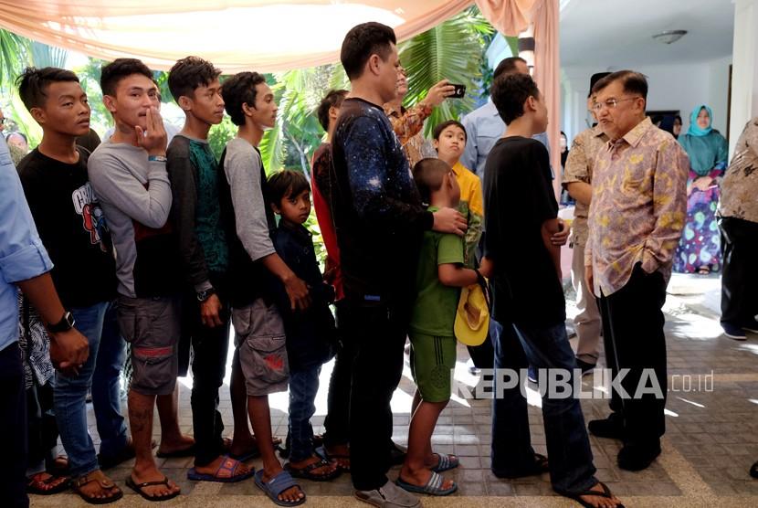 Wakil Presiden Jusuf Kalla (kanan) menerima warga saat menggelar Halalbihalal di kediamannya di Jalan Haji Bau, Makassar, Sulawesi Selatan, Ahad (17/6).