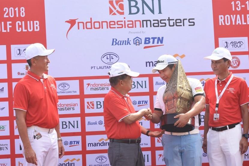 Wakil Presiden Jusuf Kalla (kedua kiri) menyerahkan Piala BNI Indonesian Masters 2018 kepada pegolf Thailand Poom Saksansin (kedua kanan) disaksikan oleh Founder Indonesian Master and Chairman of Asia Tour Jimmy Masrin (kiri) dan Wakil Direktur Utama BNI Herry Sidharta (kanan) seusai memenangkan turnamen golf tersebut di Jakarta, Minggu (16/12/2018).
