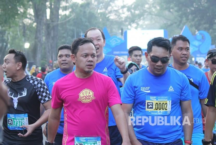 Wali Kota Bogor Bima Arya Sugiarto dan Wali Kota Bandung Ridwan Kamil memasuki garis finis dalam ajang Bandung West Java Marathon 2018 yang digelar Pocari Sweat bersama Bank BJB, Pemprov Jawa Barat dan Pemkot Bandung, Ahad (22/7).