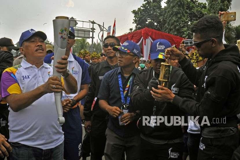 Wali Kota Cilegon Edy Aryadi (kiri) mengangkat obor saat Torch Relay Asian Games 2018 melintasi Kota Cilegon di Cilegon, Banten, Kamis (9/8).