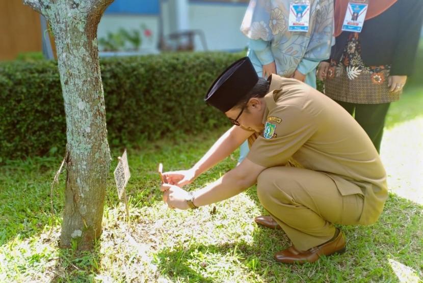 Wali Kota Sukabumi Achmad Fahmi melakukan scan barcode pohon di SMA 2 Sukabumi Senin (8/4). Sekolah tersebut mengembangkan aplikasi untuk mempermudah pembelajaran di sekolah melalui digitalisasi pohon.