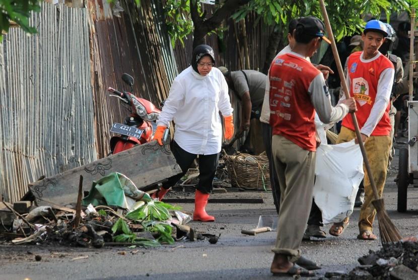 Wali Kota Surabaya Tri Rismaharini (kiri) membersihkan jalan dari sampah di kawasan Jembatan Merah, Surabaya Jawa Timur, Senin (18/7).