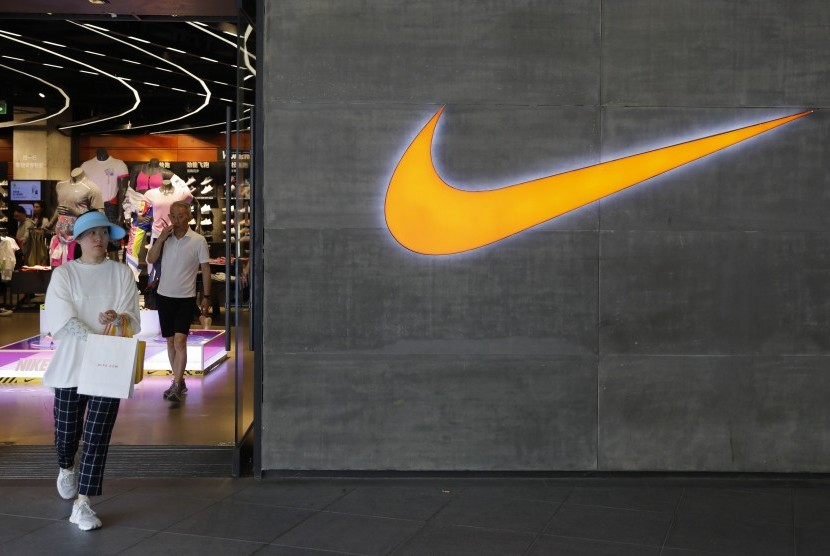 Wanita berjalan melalui gerai Nike di Beijing, China.