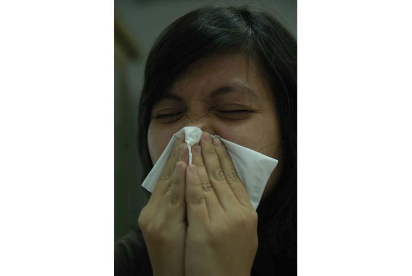 Wanita bersin dan sedang flu (ilustrasi).