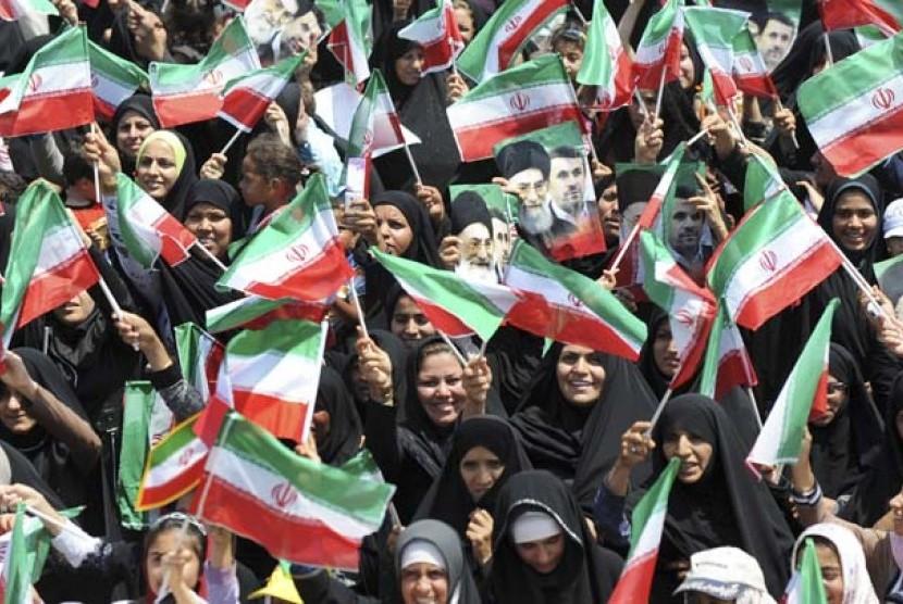 Wanita Iran mengibarkan bendera Iran.