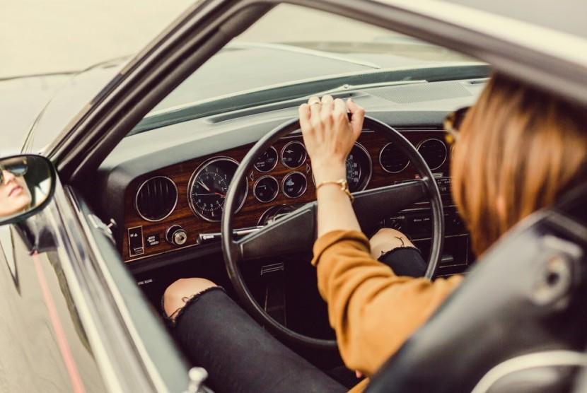 Wanita mengemudi mobil.