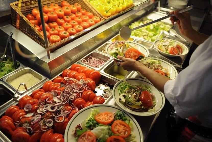 Wanita menuang saus ke atas sayuran salad.