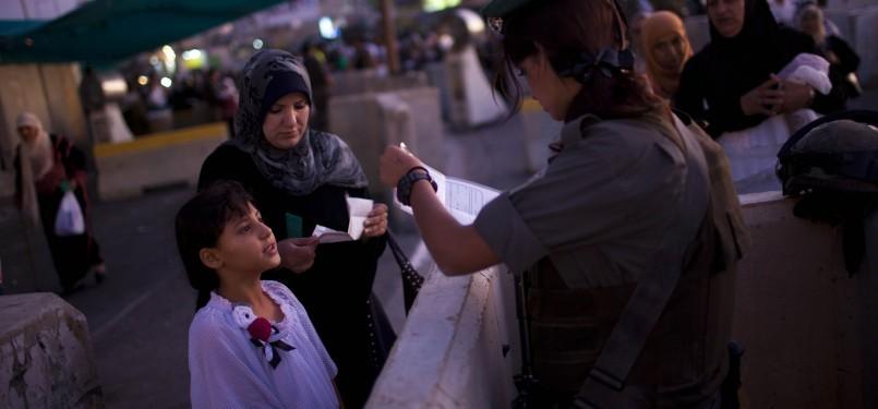 Wanita Palestina dan anaknya menjalani pemeriksaan oleh serdadu Israel di pos penyeberangan Qalandia, Jumat (5/8). Warga Palestina asal Tepi Barat berbondong-bondong menuju Masjid Al Aqsa di Yerussalem (Ilustrasi)