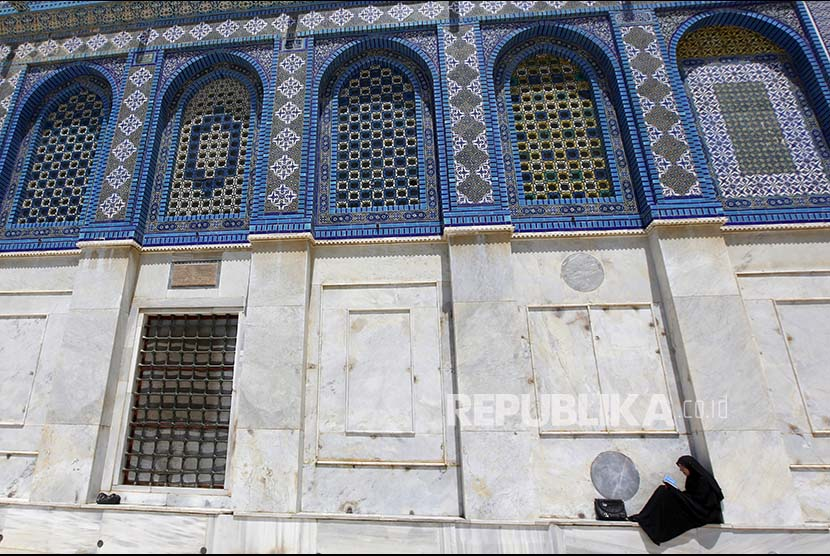 Wanita palestina membaca Alquran di area kompleks Masjid Al Aqsa.