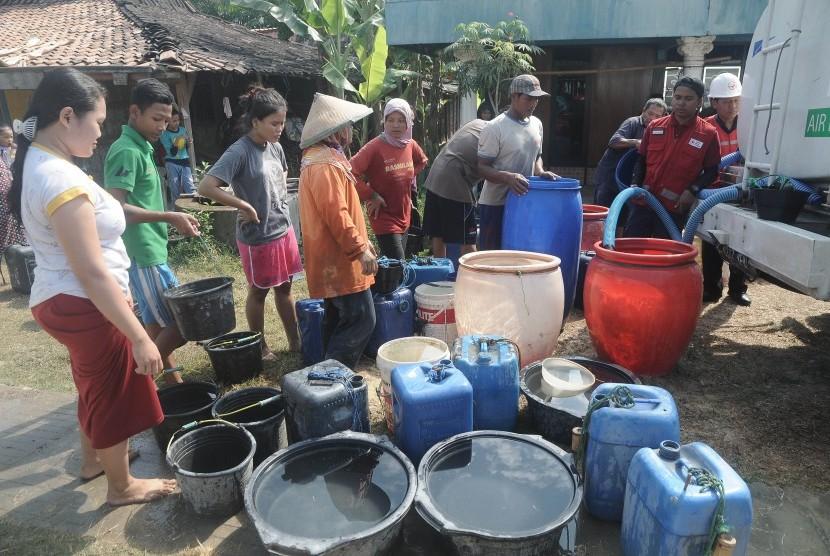 Warga antre mendapatkan air bersih dari truk tangki Palang Merah Indonesia (PMI) di Dusun Clepat, Toroh, Grobogan, Jawa Tengah, Rabu (3/7/2019).