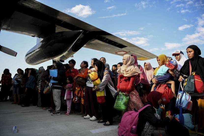 Warga antre untuk dievakuasi menggunakan pesawat Hercules di Bandara Mutiara Sis Al Jufri Palu, Sulawesi Tengah, Minggu (30/9).
