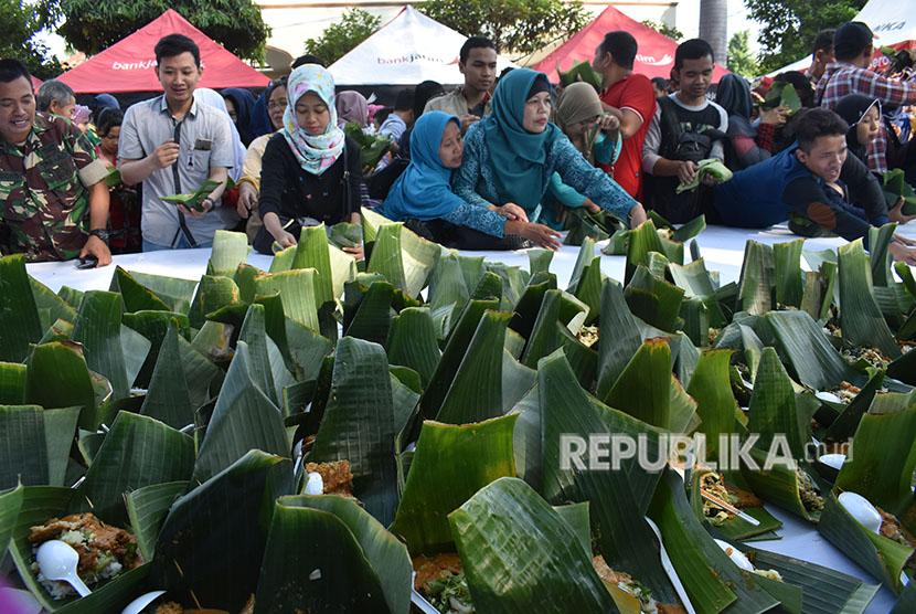Warga antre untuk mendapatkan nasi pecel gratis saat digelar Festival Pecel Pincuk di Kota Madiun, Jawa Timur, Jumat (22/6).