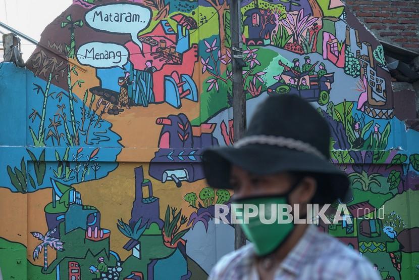 Warga berada di dekat mural karya Yudha Sandy di Jalan Ibu Ruswo, Gondomanan, Yogyakarta, Senin (20/9/2021). Festival Kebudayaan Yogyakarta (FKY) 2021 dengan tema Mereka Rekam berlangsung hingga 7 Oktober 2021 secara daring sebagai upaya pendokumentasian kebudayaan Yogyakarta.