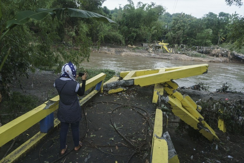 Warga beraktivitas di dekat jembatan yang rusak di Imogiri, Bantul, DI Yogyakarta, Kamis (30/11). Banyak jembatan penghubung antardesa di DIY dan wilayah Jawa Tengah putus diterjang banjir menyusul dampak dari siklon tropis Cempaka..