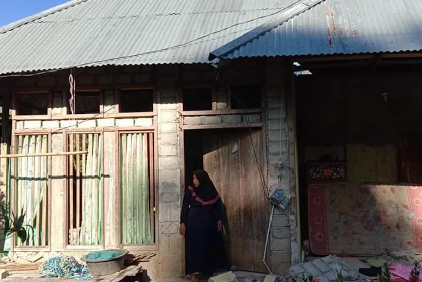 Warga beraktivitas di rumahnya yang rusak akibat gempa di Desa Tomara, Halmahera Selatan, Maluku Utara, Senin (15/7/2019).