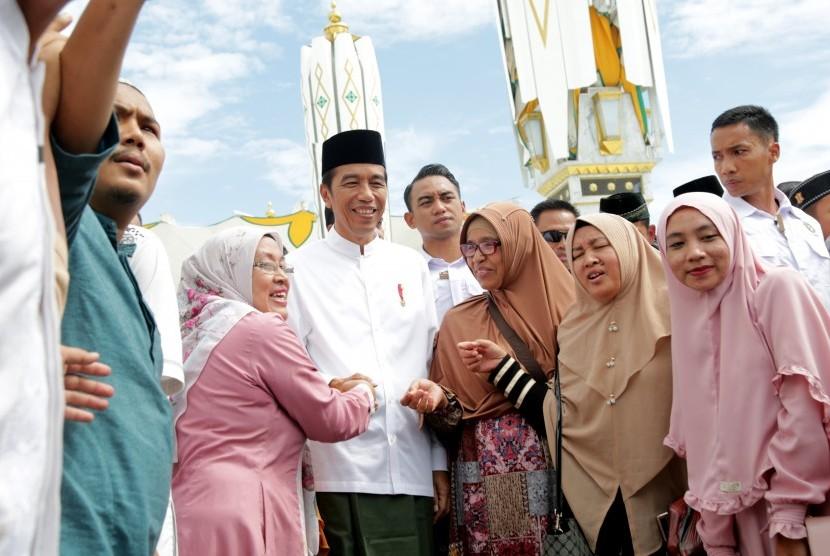 Warga berfoto dengan Presiden Joko Widodo setelah penyerahan sertifikat tanah wakaf kepada pengurus masjid, mushola dan pasantren seusai melaksanakan ibadah Jumat di Banda Aceh, Aceh, Jumat (14/12/2018).