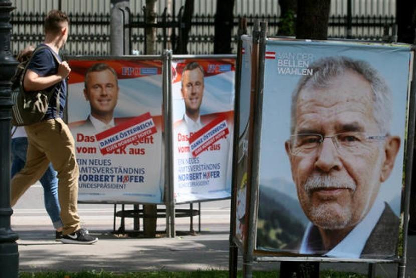 Warga berjalan di antara poster kampanye kandidat presiden Austria dan mantan ketua Partai Hijau Alexander Van der Bellen (kanan), dan kandidat presiden dari Partai Kebebasan Norbert Hofer (kiri), Senin, 23 Mei 2016.
