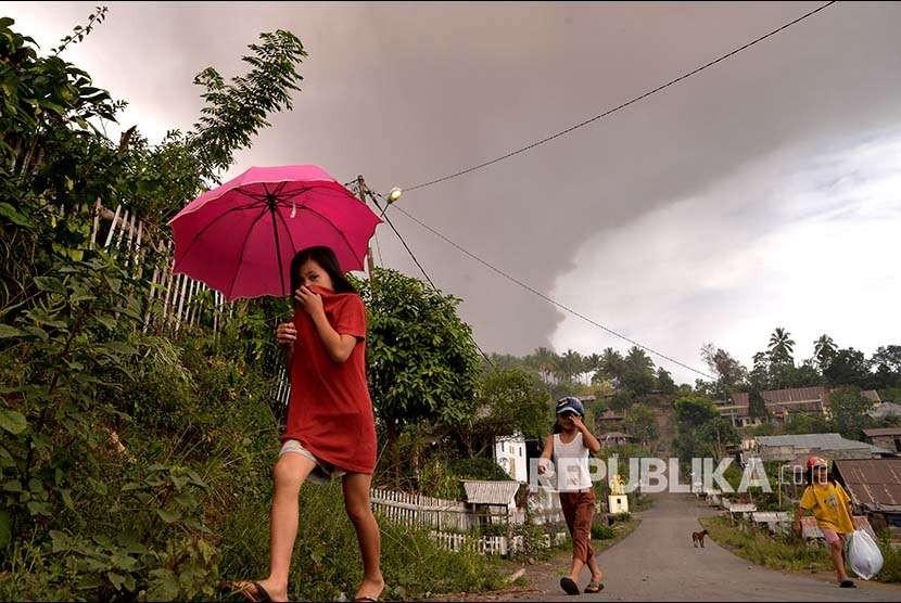 Warga berjalan di bawah hujan abu vulkanik setinggi 5.809 mdpl berwarna kelabu akibat letusan gunung Soputan, di atas Desa Kota Menara, Minahasa Selatan, Sulawesi Utara, Rabu (3/10).
