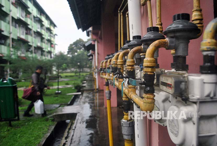 Warga berjalan di belakang meteran jaringan gas Perusahaan Gas Negara (PGN) di Rumah Susun Sewa (Rusunawa) Menteng, Bogor, Jawa Barat, Selasa (6/3). PT PGN menyalurkan gas alam ke 320 jaringan pipa di empat