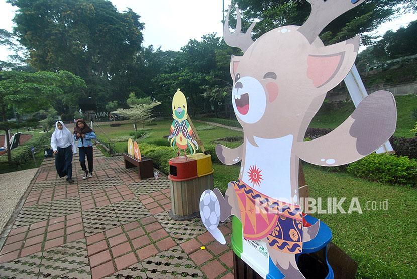 Warga berjalan di samping maskot Asian Games 2018 di Taman Sempur, Kota Bogor, Jawa Barat, Sabtu (19/5).