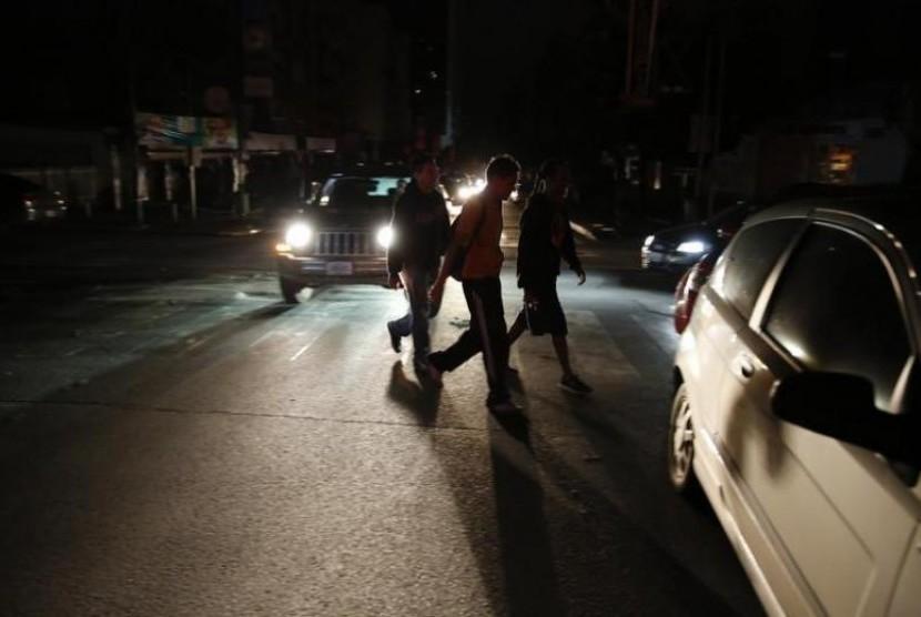 Warga berjalan di tengah kegelapan akibat listrik padam di Caracas, Venezuela.
