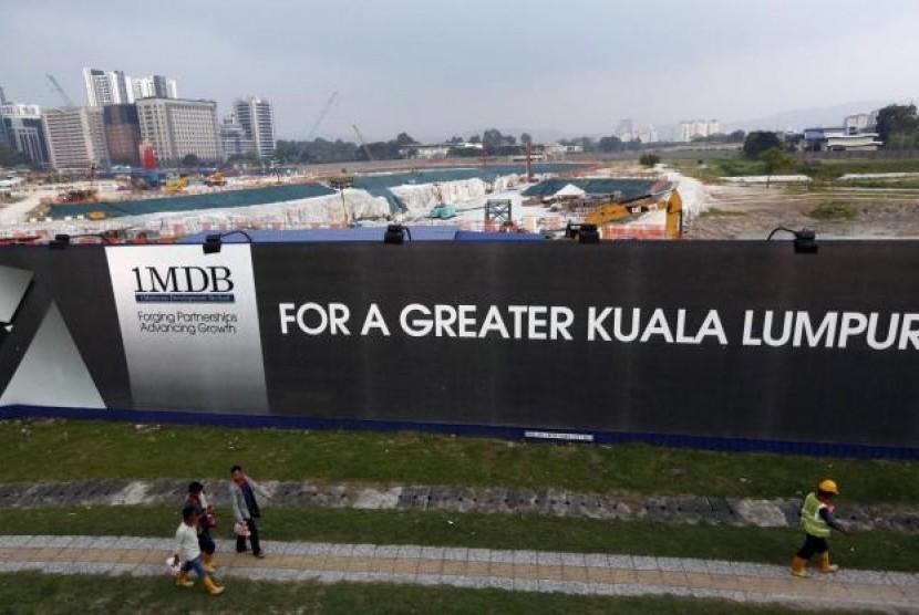 Warga berjalan melewati logo 1Malaysia Development Berhad (1MDB) di Kuala Lumpur, Malaysia.