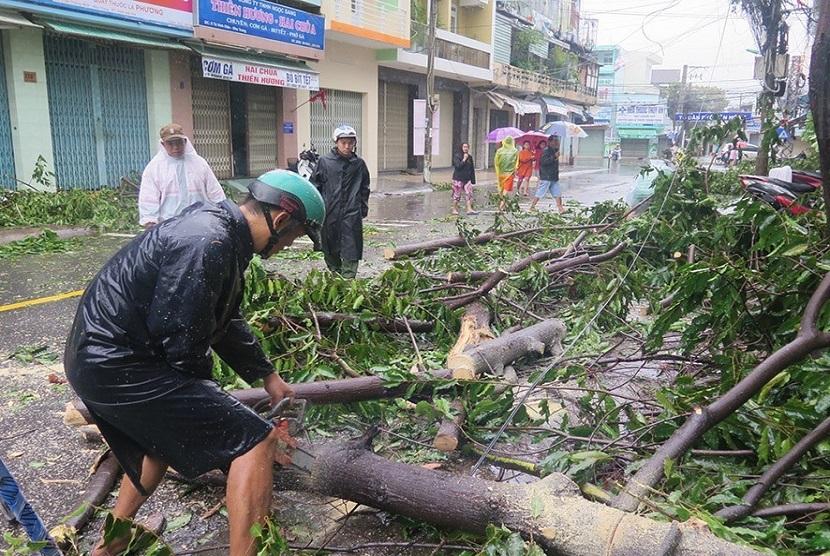 Warga berjalan melewati pohon yang tumbang akibat topan Damrey, di Nha Trang, Khanh Hoa, 4 November 2017. Topan ini menyebabkan 11 orang tewas