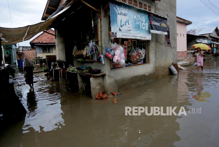 Warga berjalan menembus genangan air akibat banjir.