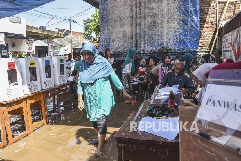 Warga berjalan menuju bilik suara di TPS 16 Pemilu 2019 yang terdampak banjir di Kampung Bojongasih, Kecamatan Dayeuhkolot, Kabupaten Bandung, Rabu (17/4).