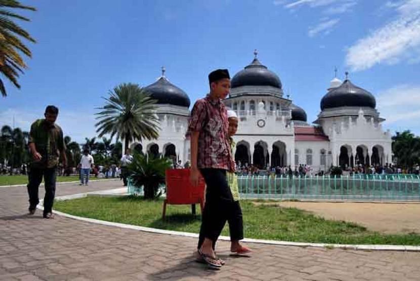 Warga berjalan usai menunaikan shalat Jumat di Masjid Raya Baiturrahman, Banda Aceh.
