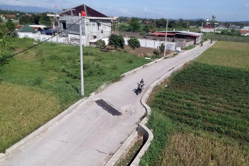 Warga berkendara di jalan yang dibangun mengunakan dana desa 2018, di Desa Laladon, Bogor, Jawa Barat, Jumat (28/12/2018).