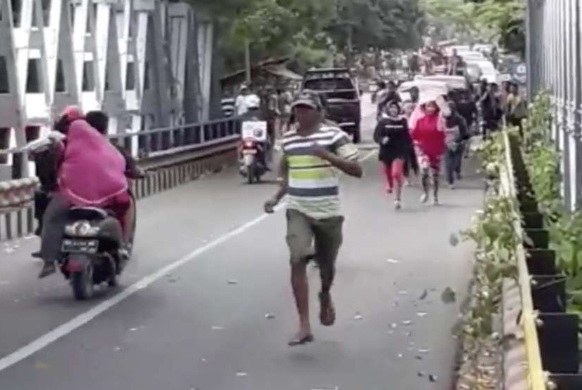 Warga berlarian karena panik akibat jembatan Beli di Lombok Utara retak akibat gempa bumi kembali mengguncang Lombok