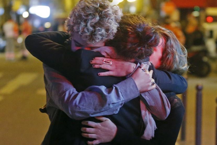 Warga berpelukan setelah lepas dari aksi teror di Bataclan Concert Hall, Paris, Prancis, Sabtu (14/11).
