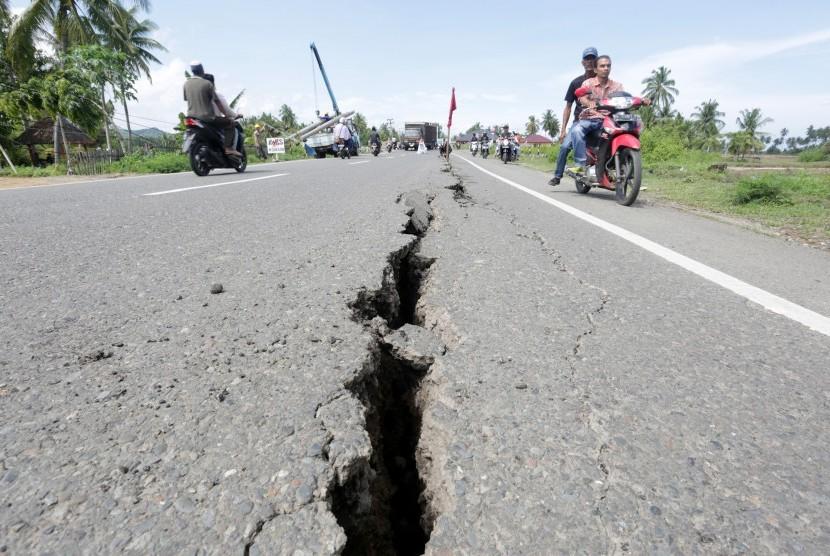 Warga bersepeda motor melaju di jalanan yang rusak (ilustrasi)