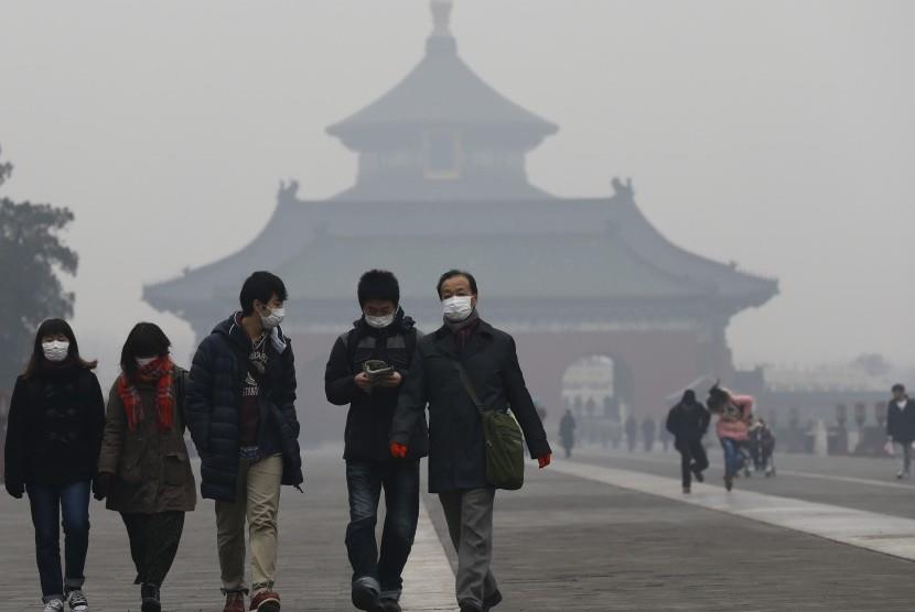 Warga Cina mengenakan masker untuk menghindari polusi udara di Beijing.