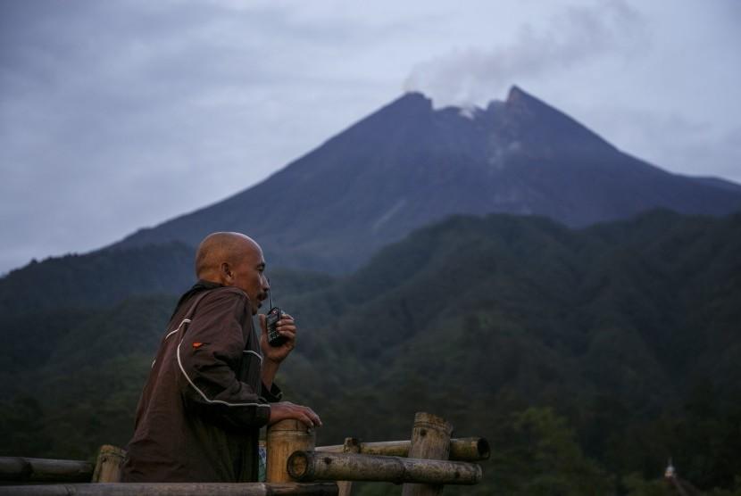 Warga dari komunitas siaga Merapi menggunakan alat radio komunikasi memantau puncak Gunung Merapi dari pos pantau Klangon, Cangkringan, Sleman, DI Yogyakarta.