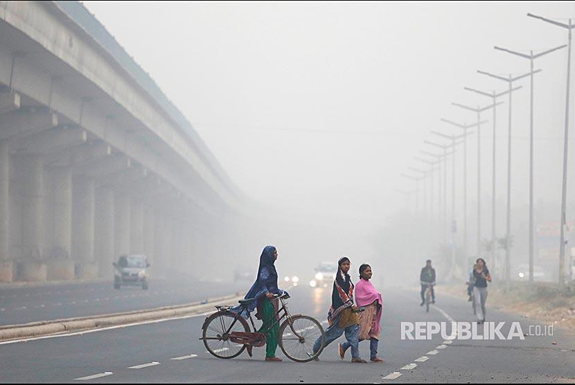 Warga Delhi menyeberangi jalanan di New Delhi yang tersaput kabut asap. Pemerintah India belum menargetkan tahun berapa negaranya bisa mencapai nol emisi.