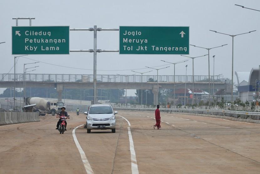 Warga dengan menaiki sepeda motor melintasi ruas Tol Jakarta Outer Ring Road West 2 (JORR W2) seksi Ciledug - Ulujami, Jakarta Selatan, Kamis (26/6). PT Jasa Marga Tbk memastikan ruas Tol Jakrta Outer Ring Road West 2 (JORR W2) seksi Ciledug - Ulujami yang
