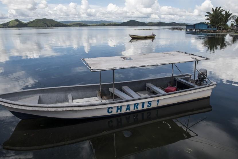 Warga dengan perahu kecil melintas di kawasan Khalkote, Jayapura, Papua, Senin (13/11). Kawasan Khalkote di danau Sentani akan menjadi pusat kemeriahan pelaksanaan olahraga air pada PON 2020 di Papua.