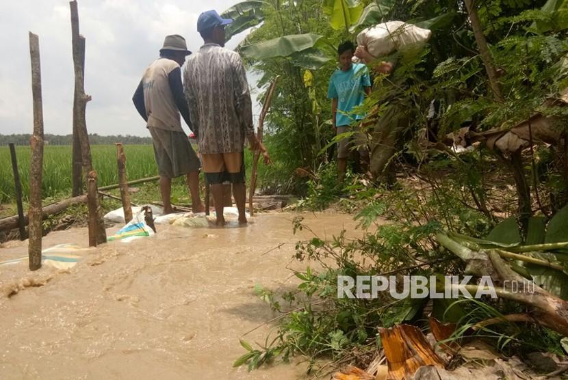 Warga di Blok Como, Desa Pilangsari, Kecamatan Jatibarang, Kabupaten Indramayu  bergotong royong menambal rembesan sungai Cimanuk dengan menggunakan karung tanah dan pasir, Jumat (23/2).