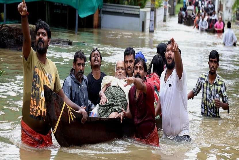 Warga di India menggunakan perahu karet untuk menyelamatkan seorang kakek yang terjebak banjir di Kochi, Negara Bagian Kerala, Jumat (17/8). Wilayah ini mengalami banjir parah sehingga sekolah dan perkantoran terpaksa diliburkan. Banjir terjadi akibat meluapnya air di Sungai Periyar