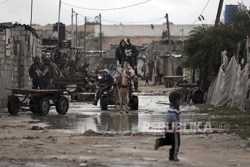 Warga di Kamp Pengungsi Jabaliya mengendarai kereta keledai di utara Jalur Gaza, Kamis (16/2).