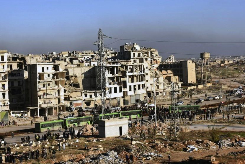 Warga di kawasan timur Aleppo, Suriah, berkumpul dekat bus hijau untuk berangkat menuju lokasi evakuasi.