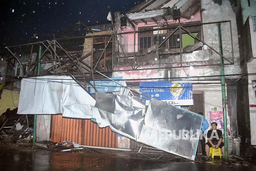 Warga duduk di depan rukonya yang rusak diterjang angin puting beliung di wilayah Batu Tulis, Bogor, Jawa Barat, Kamis (6/12)