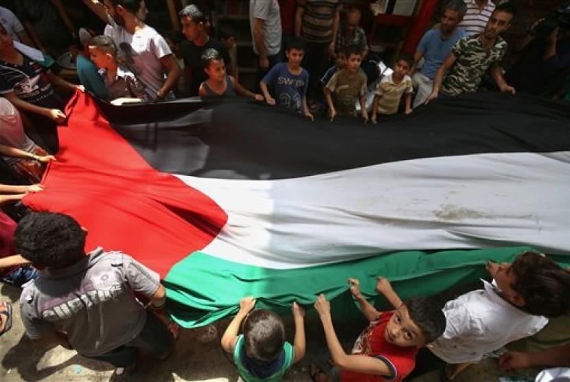 Warga Gaza membentangkan bendera Palestina.